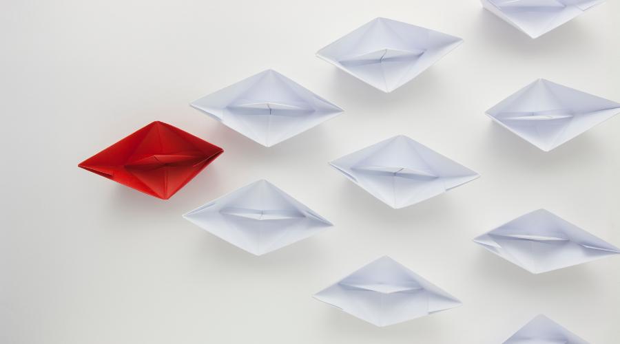 Dekoratives Foto auf dem ein rotes, gefaltetes Papierschiff an der Spitze einer Gruppe weißer Papierschiffe schwimmt.